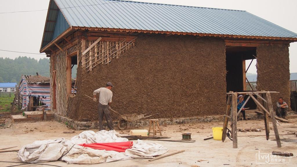 这位大叔正在盖房子,看得清楚,木头架子,泥巴房.