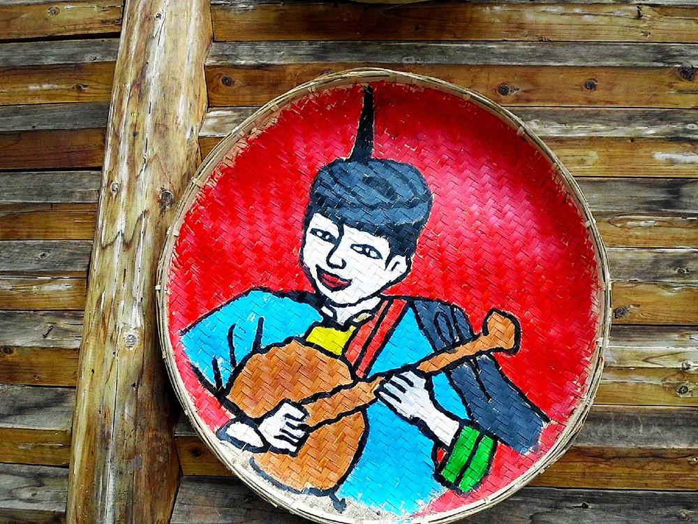 墙上挂着民族艺人的绘画作品,色彩艳丽的民族风人物图片图片