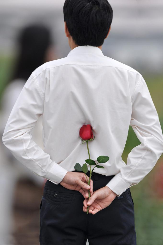 男人手放后拿着玫瑰送给不远处的女人图片