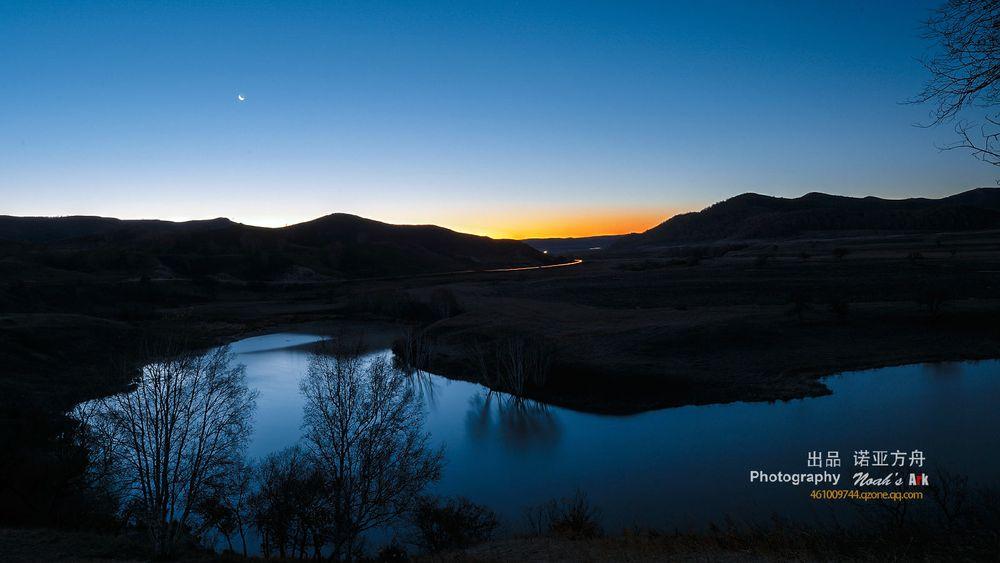 水面反射着天空的蓝色,远山,近水,月亮,车灯聚集在同一画面,景象是图片